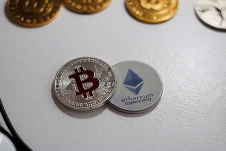 Digital currency physical grey Ethereum coin near gold bitcoins. Stock Photo