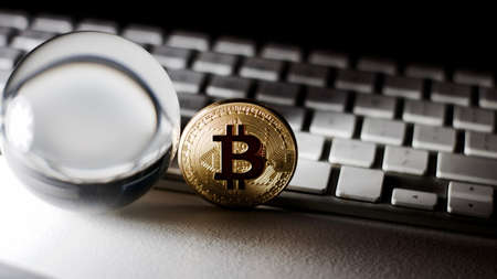 Digital currency physical metal bitcoin coin on the white keyboard near glass ball.