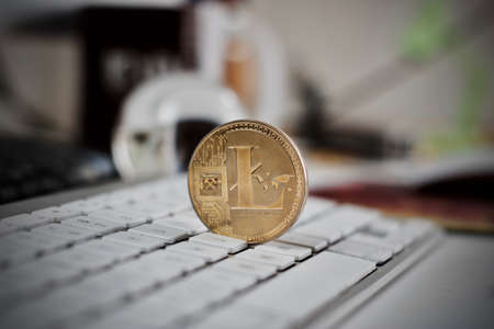 peer to peer: Digital currency physical litecoin coin on the white keyboard. Computer concept.