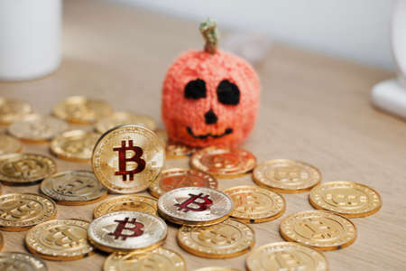 Digital currency physical metal bitcoin coin. Halloween pumpkin concept.
