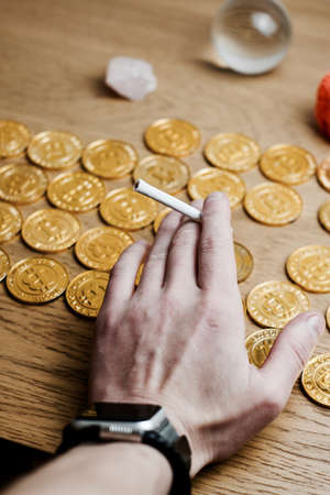 Man hand with a joint near bitcoin gold coins on the table.