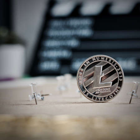 Digital currency physical metal litecoin coin. Cryptocurrency video concept. Stock Photo