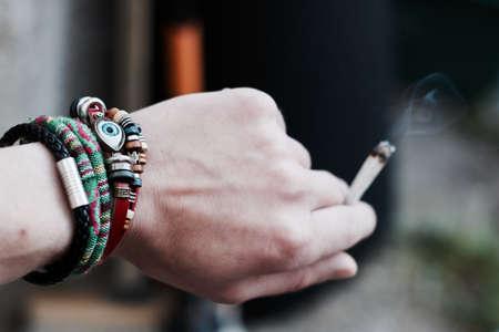 Small spliff in man hand. Marijuana smoking concept.
