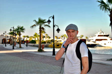 White young man on holiday in Egypt. Palm tree, boats, sun and relax time. Stock Photo
