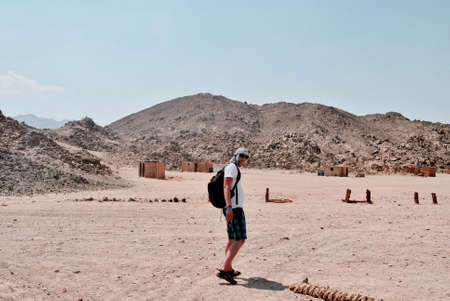 Young white man on the desert in Egypt. Sunny day and stones mountains. Stock Photo