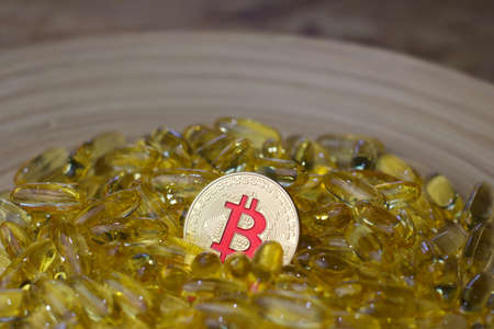 Digital currency physical metal bitcoin coin and yellow pills. Medical bitcoin concept.