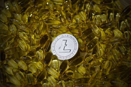 Digital currency physical metal litecoin coin and yellow drugs. Medical cryptocurency litecoin concept.