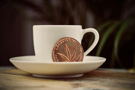 Metal brass marijuana coin. Cannabis coffee concept. Stock Photo