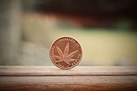 Physical metal brass marijuana coin. Cannabis coin concept.