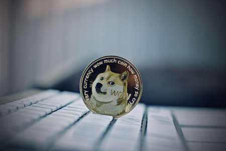 Digital currency physical metal dogecoin coin on white computer keyboaed. Stock Photo