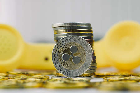 Digital currency physical metal ripple coin. Yellow phone communication concept.