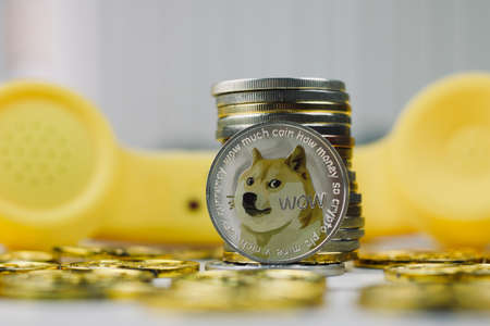 Digital currency physical metal dogecoin coin. Yellow phone communication concept.