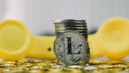 Digital currency physical metal litecoin coin. Yellow phone concept.
