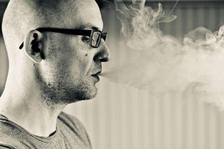 Young bald man smoking e-cigarette to quit tobacco. Vapor and alternative nicotine free smoking concept.