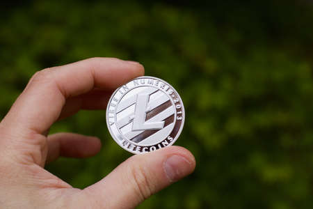 Digital currency physical metal silver litecoin coin. Cryptocurrency outdoor concept.