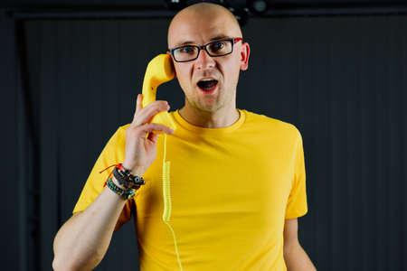 Bald young man in yellow tshirt. Tshirt mockup concept.