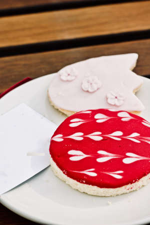 Sweet tasty cookies on white plate with a ticket. Sweet food concept.
