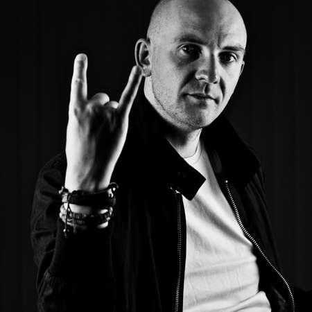 Bald young man in tshirt show corners on hand. Tshirt mockup concept.