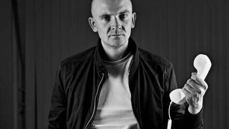 Bald young man in tshirt. Tshirt mockup concept. Phone. Stock Photo