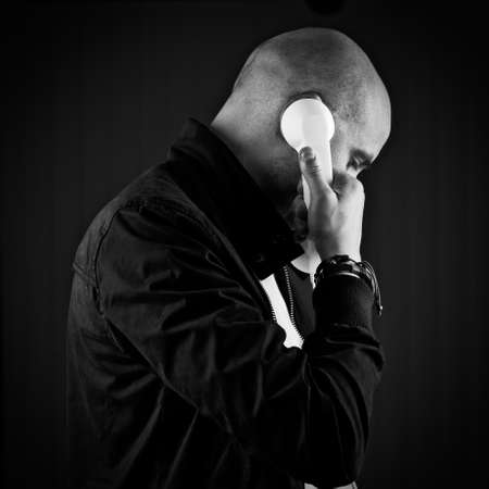 Bald young man in black with phone. Stock Photo