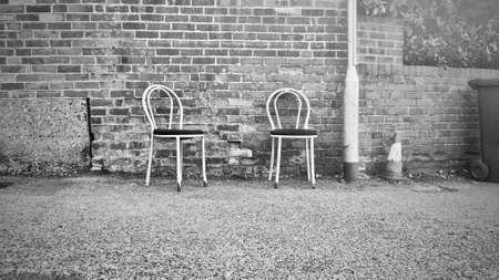 Old wall and two chairs near pizza house. Reading, England.