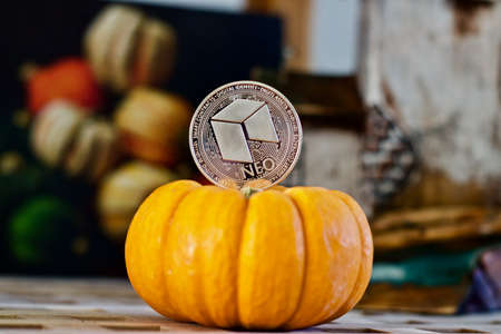 Digital currency physical silver metal neo coin. Orange halloween concept. Stock Photo