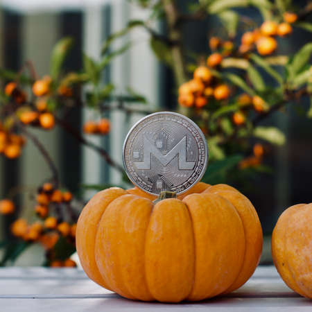 Digital currency physical metal monero coin. Cryptocurrency halloween concept. Stock Photo