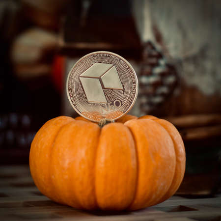 Digital currency physical silver metal neo coin. Orange halloween concept. Editorial