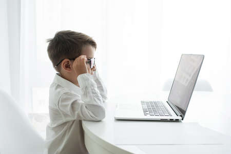 Cute little boy using laptop while doing homework against white background Фото со стока