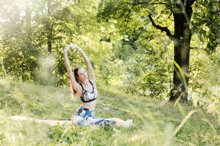 the girl is engaged in fitness and meditates in the park city