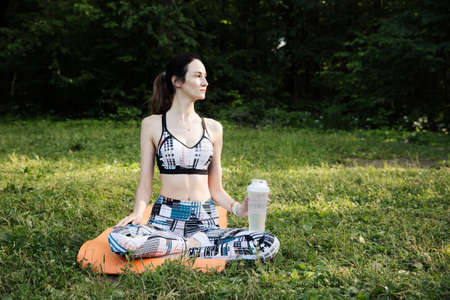 the girl is engaged in fitness and meditates in the park city Stock fotó