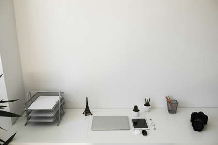office table on which laptop, coffee, tablet, camera and other items