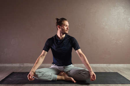 Young sporty man practicing yoga, meditating in Half Lotus pose, working out, wearing sportswear, indoor full length, gray yoga studio Stok Fotoğraf