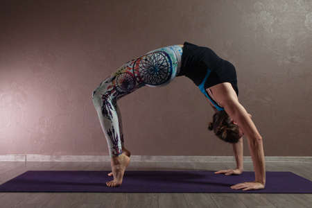 Young sporty attractive woman practicing yoga, meditating in yoga pose, working out, wearing sportswear, indoor full length, brown yoga studio Stok Fotoğraf