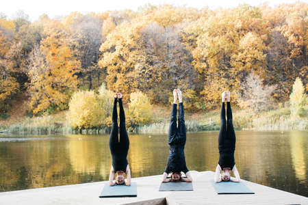 Young women and man doing yoga asana in the nature with the lake view. Evening workout outdoors, sports and healthy lifestyle. Yoga