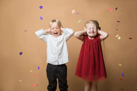 a boy and a girl stand on an orange background with their hands over their ears and shout from a confetti firecracker