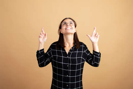 A young woman in a plaid dress stands on an orange background and shows different emotions Stock Photo