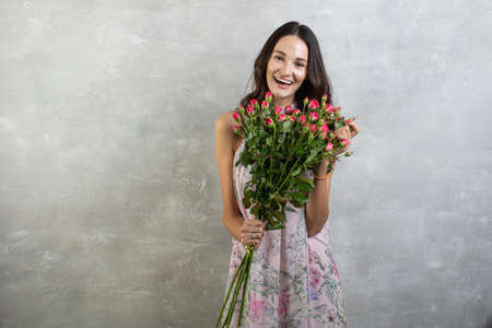 Close-up portrait of attractive young woman in summer dress holding bouquet of roses, girl happy