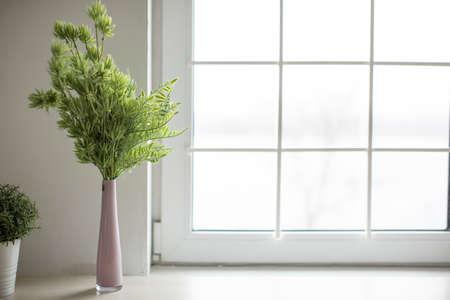 Jarrón rosa con ramitas verdes se encuentra en una cocina luminosa y acogedora. Cocina Foto de archivo