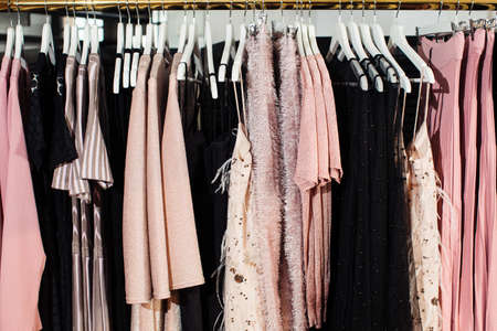 Close-up view of various stylish clothes hanging on hangers in boutique. Clothes