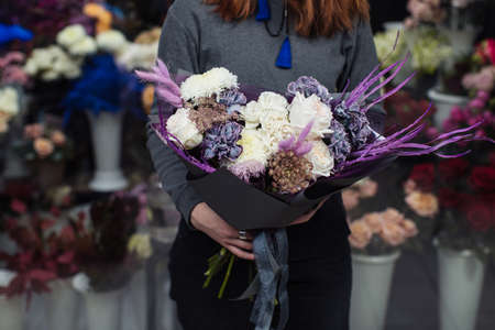 Beautiful bouquet of mixed flowers with peonies. The work of the florist. Flower delivery Stock Photo