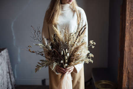 Beautiful autumn bouquet of dry materials in the hands of a woman Stock Photo