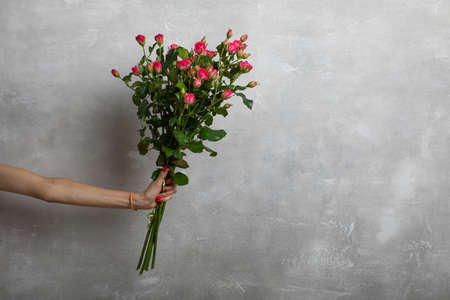 Hand of a young girl holding a bouquet of pink roses