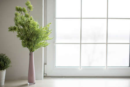 Pink vase with green twigs stands in a bright cozy kitchen