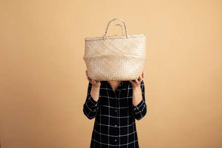 A young woman in a plaid dress stands with a wicker bag on an orange background Stock Photo