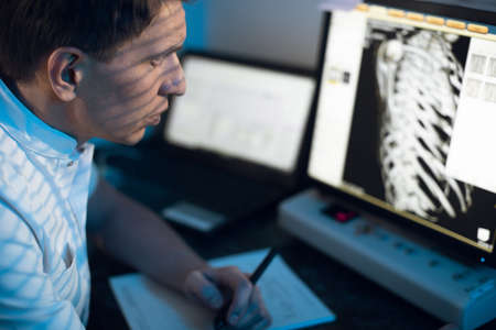 in medical laboratory patient undergoes MRI or CT scan process under Supervision of Radiologist in Control Room, He Watches Procedure and Monitors skeleton and ribs of the patient Zdjęcie Seryjne