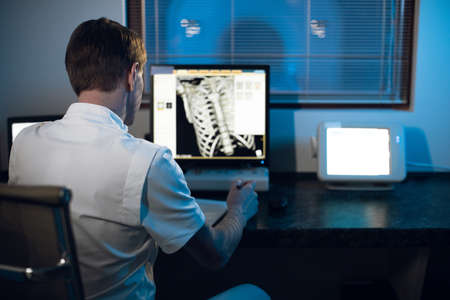 in medical laboratory patient undergoes MRI or CT scan process under Supervision of Radiologist in Control Room, He Watches Procedure and Monitors skeleton and ribs of the patient Фото со стока