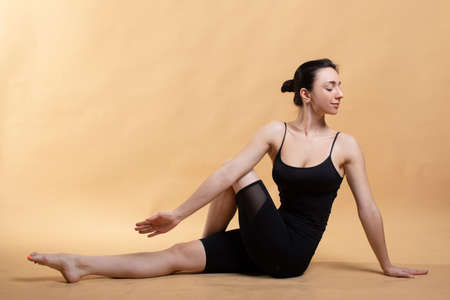 Side view portrait of beautiful young woman wearing white tank top working out against orange background, doing stretching.