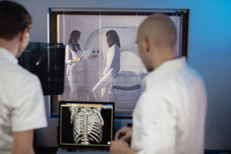 In Control Room Doctor and Radiologist Discuss Diagnosis while Watching Procedure, In the Background Patient Undergoes MRI or CT Scan Procedure