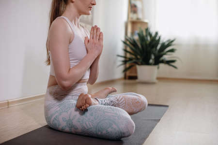 Young sporty attractive woman practicing yoga, meditating in yoga pose, working out, wearing sportswear, indoor full length, light yoga Studio